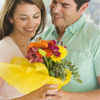 Royalty-Free Stock Photo: Husband giving wife flowers and smiling