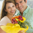 Husband and wife holding flowers and smiling - Foto Stock