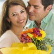 Husband and wife holding flowers and smiling — Stock Photo #4778220