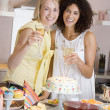 Two women at party holding drinks standing by food table smiling — Stock Photo