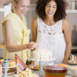 Two women at party putting candles in cake smiling — Stock Photo
