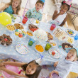 Young children at party sitting at table with food smiling — Stock Photo
