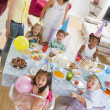 Young children at party with mothers sitting at table with food — Stock Photo #4778263