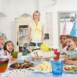 Young children at party sitting at table with mother carrying ca — Stockfoto