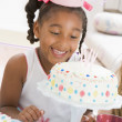 Young girl wearing party hat looking at cake smiling — Stock Photo