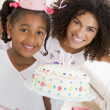 Mother and daughter with birthday cake smiling — Stock Photo #4778269