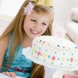 Stock Photo: Young girl wearing party hat looking at birthday cake smiling