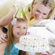 Mother and daughter with birthday cake smiling — Stock Photo