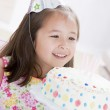 Young girl wearing party hat looking at birthday cake smiling — Stock Photo