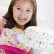 Stock Photo: Young girl wearing party hat with birthday cake smiling