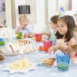 Young children at party sitting at table with food smiling — Stock Photo #4778279