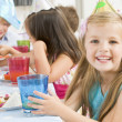 Young girl at party sitting at table with food smiling — Stock Photo