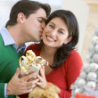 Stock Photo: Husband Surprising Wife With Christmas Present