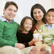 Family Sitting On Sofa Together,Holding A Christmas Gift — Stock Photo