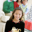 Young Girl Standing Holding Christmas Present,With Her Parents A — Stockfoto