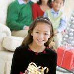 azienda di giovane ragazza in piedi regalo di Natale, con i suoi genitori un — Foto Stock