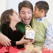 pai sendo dado um presente de Natal por sua filha e filho — Foto Stock