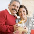 Middle Aged Couple Sitting On Sofa Holding Christmas Present — Stock Photo #4778324