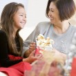 Grandmother And Granddaughter Exchanging Christmas Gifts - Stock Photo