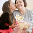 Granddaughter Kissing Grandmother On The Cheek,And Giving Her A — Stockfoto