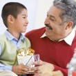 Boy Surprising Father With Christmas Present - Stock Photo
