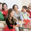 Foto Stock: Family Sitting On Sofa In Front Of Christmas Presents,Young Girl