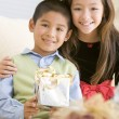Brother And Sister Sitting On Couch Holding Christmas Gift — Stock Photo
