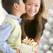 图库照片: Brother Kissing His Sister On The Cheek,And Holding A Christmas