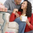 Husband And Wife Affectionately Exchanging Christmas Gifts — Stock Photo
