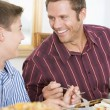 Father And Son At Christmas Dinner - Stock Photo