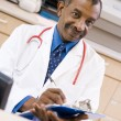 A Doctor Writing On A Clipboard At The Reception Area Of A Hospi — Foto Stock