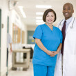 Doctor And Nurse Standing In A Hospital Corridor - Stock Photo