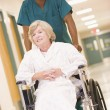An Orderly Pushing A Senior Woman In A Wheelchair Down A Hospita - Foto Stock