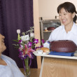 Royalty-Free Stock Photo: Nurse Serving A Patient A Meal In His Bed