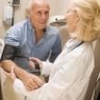 Doctor Checking Blood Pressure Of Man — Stock Photo