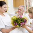 Royalty-Free Stock Photo: Young Girl Giving Flowers To Her Mother In Hospital