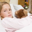 Young Girl Lying In Hospital Bed With Teddy Bear — Stock Photo #4779410