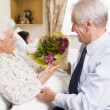 Senior Man Giving Flowers To His Wife In Hospital - Stock Photo