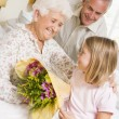 Granddaughter Giving Flowers To Her Grandmother In Hospital — Stock Photo