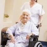 Nurse Pushing Senior Woman In Wheelchair — Stock Photo