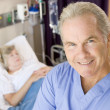 Doctor Standing And Smiling In Patients Room — Stock Photo
