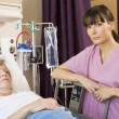 Nurse Checking Up On Patient Lying In Hospital Bed — Stock Photo #4779538