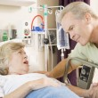 Middle Aged Man Talking To Senior Woman In Hospital - Stock Photo