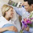 Man Giving His Pregnant Wife Flowers - Stockfoto