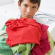 Young Boy Holding A Pile Of Laundry - Stok fotoraf