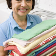 Woman Holding Folded Laundry - Stock Photo