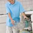 Stock Photo: Young Boy Loading Dishwasher