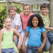 Five young friends at a playground smiling — Foto Stock