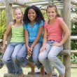 Three young girl friends at a playground smiling — Foto Stock