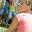 Stock Photo: Two young girl friends at playground whispering about other gi